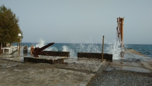 The little port of moutsouna, with some waves breaking against shore