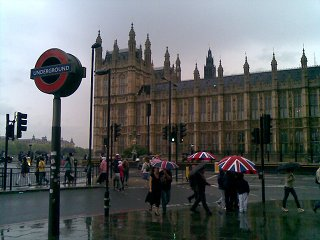 A very brittish picture, the underground + houses of parliament + a bunch of umbrellas with the union jack