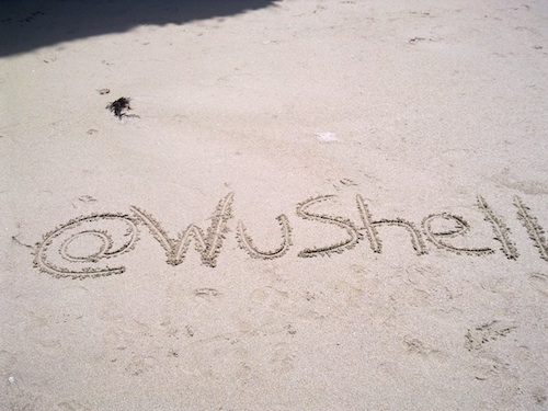 An *action shot* of my twitter ID written on the sand on a beach located in the north of Galicia